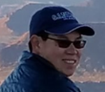 Coach Nat Couropmitree in a basecall cap and sunglasses smiling