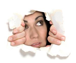 woman peeking through a hole