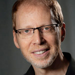 white male with glasses smiling at the camera